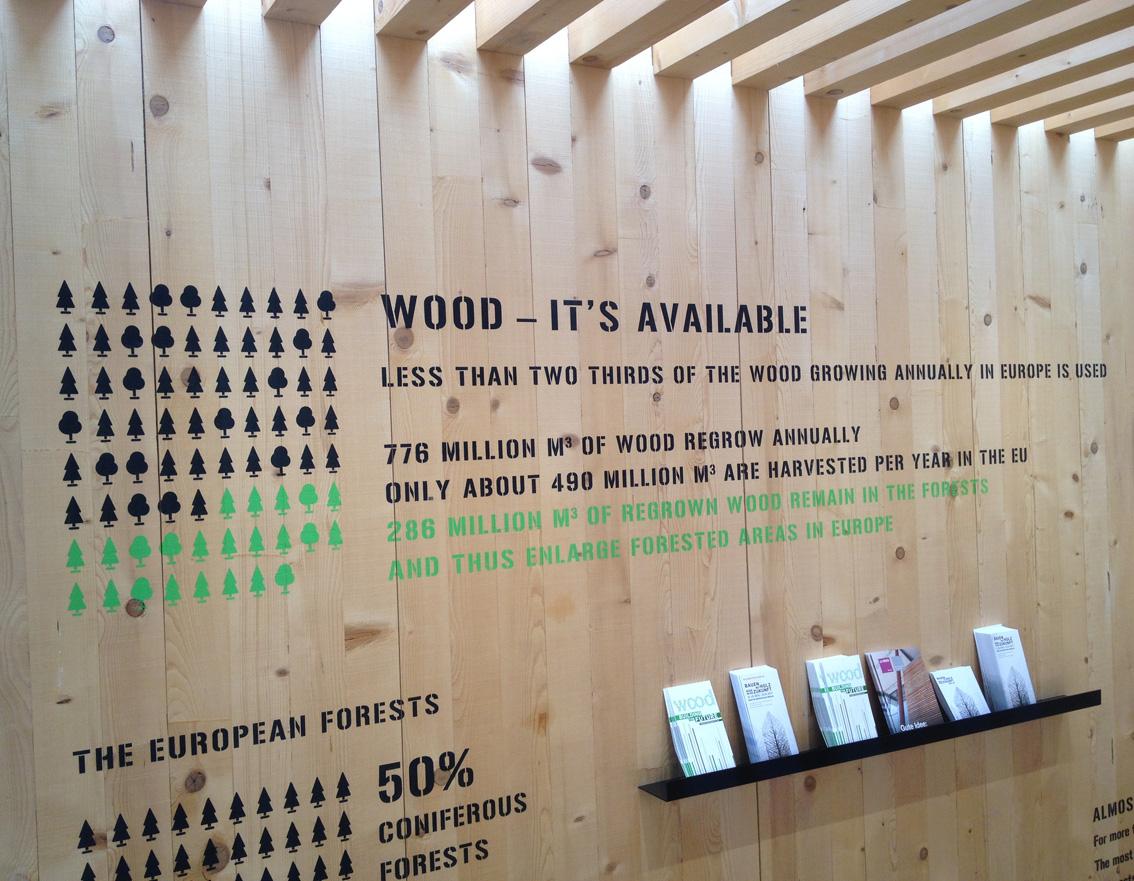 Mit einer aufgesprühten Schrift, die an Überseecontainer erinnert, werden durch einprägsame Grafiken die ökologischen Vorteile vom Baustoff Holz erläutert.