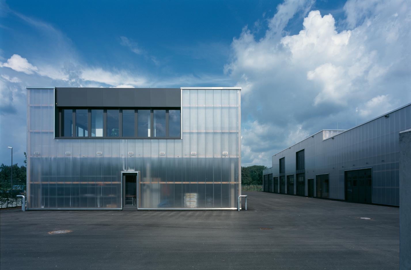 Tageslichtdurchflutete Werkstattbereiche durch Polycarbonatfassaden; hier mit durchscheinendem Stahlbetonvolumen des Verwaltungsbereiches, Foto: Florian Holzherr