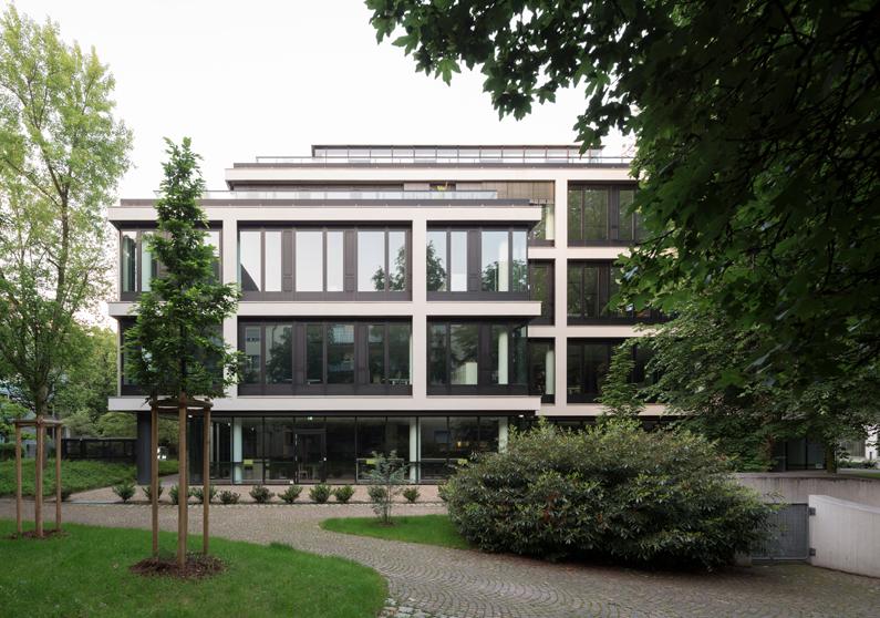 Im Gartenareal befreit sich die Fassade von Haus Nr. 9 von ihrer Strenge, mit der sie sich an der Platzfassade zeigt, Foto: Florian Holzherr
